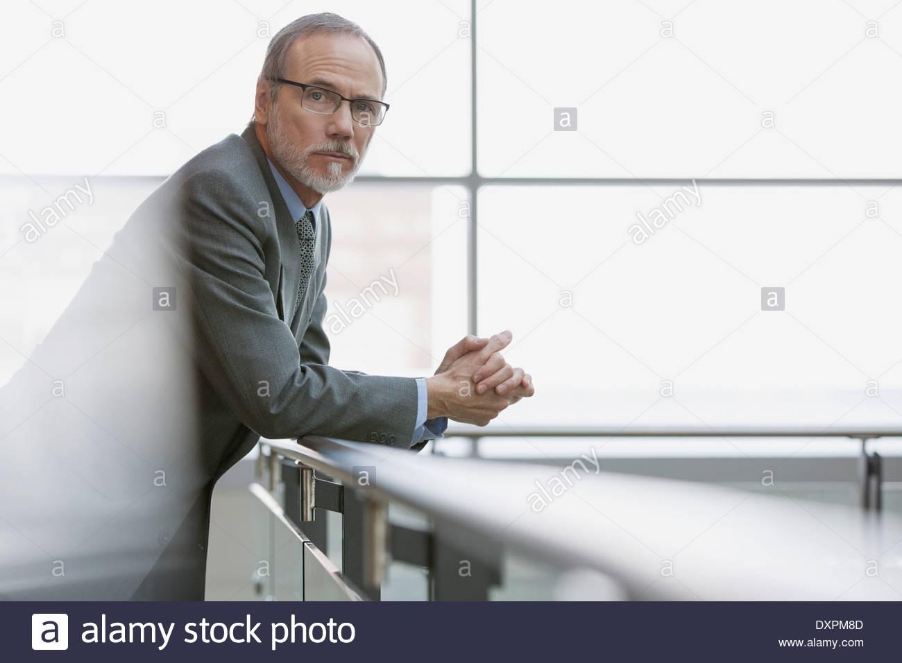 Portrait of confident businessman leaning on railing - Stock Image