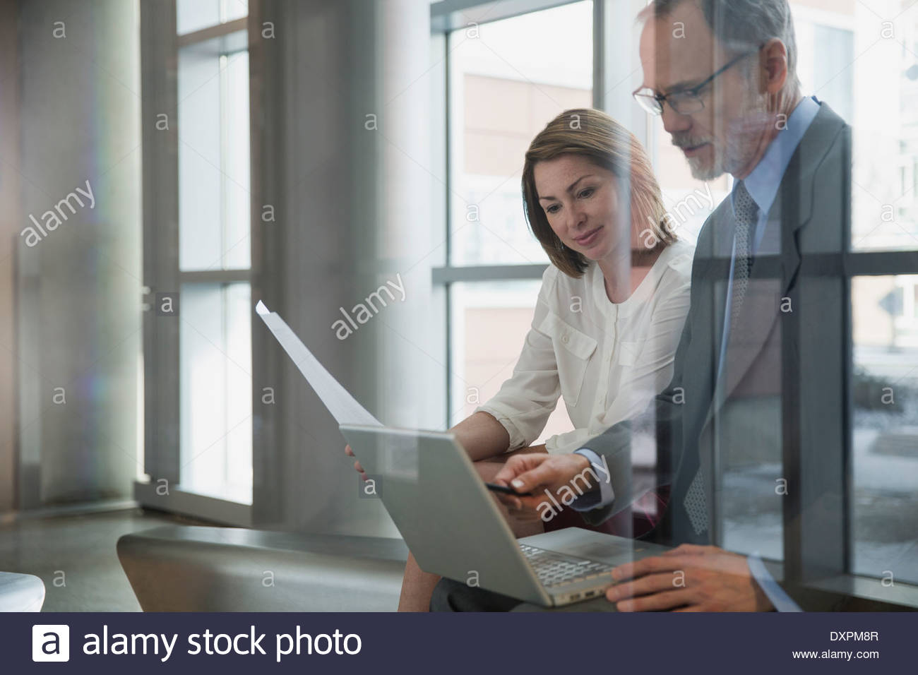 Business people using laptop in meeting - Stock Image