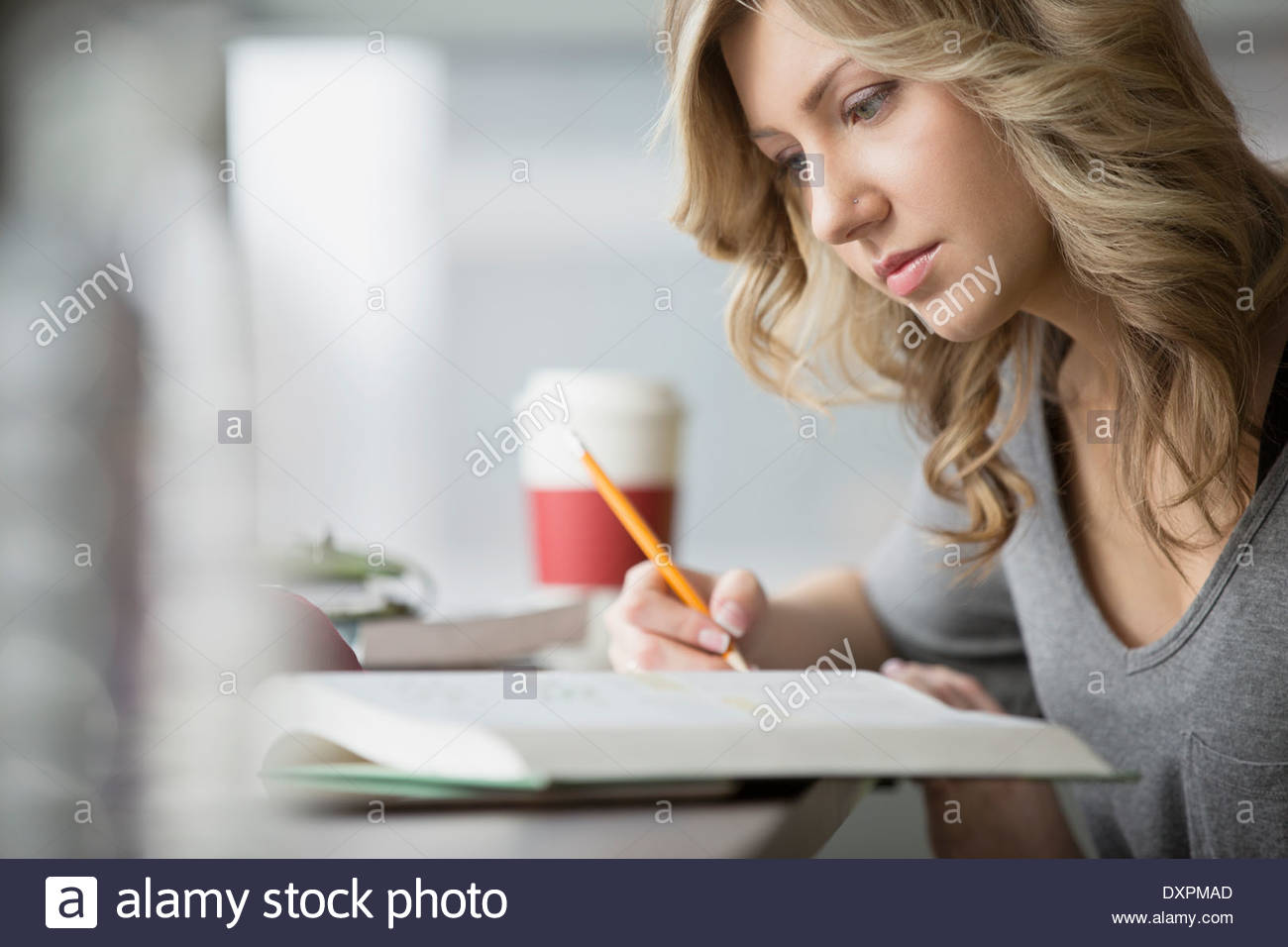 Close up of focused college student reading book - Stock Image