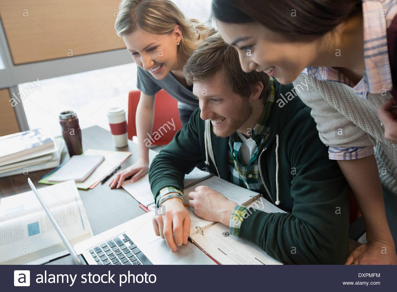 College students gathered around laptop - Stock Image