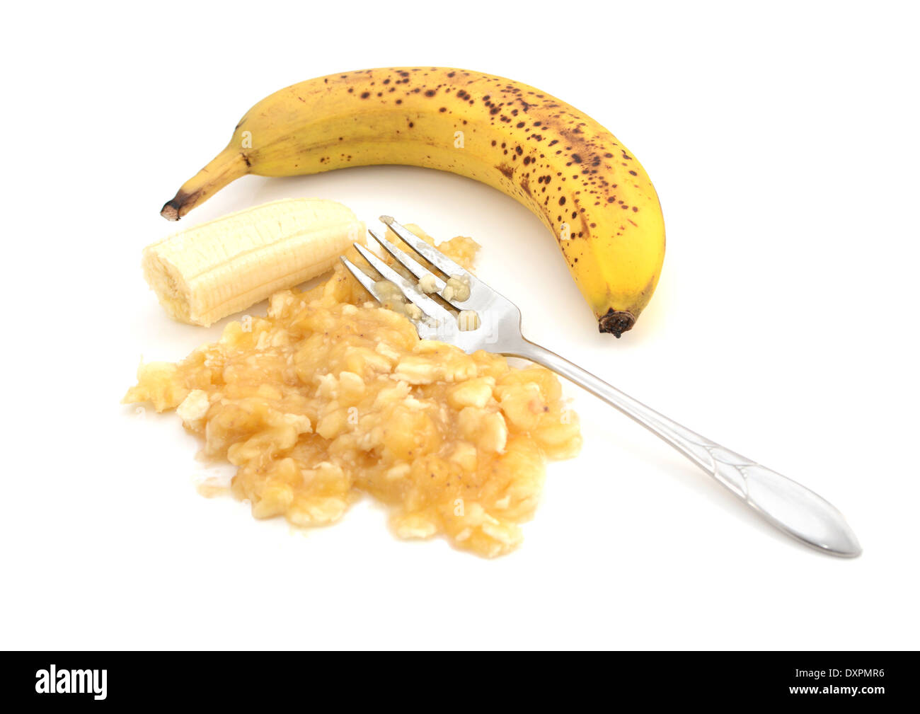 Overripe banana with a fork and pureed fruit, isolated on a white background - Stock Image