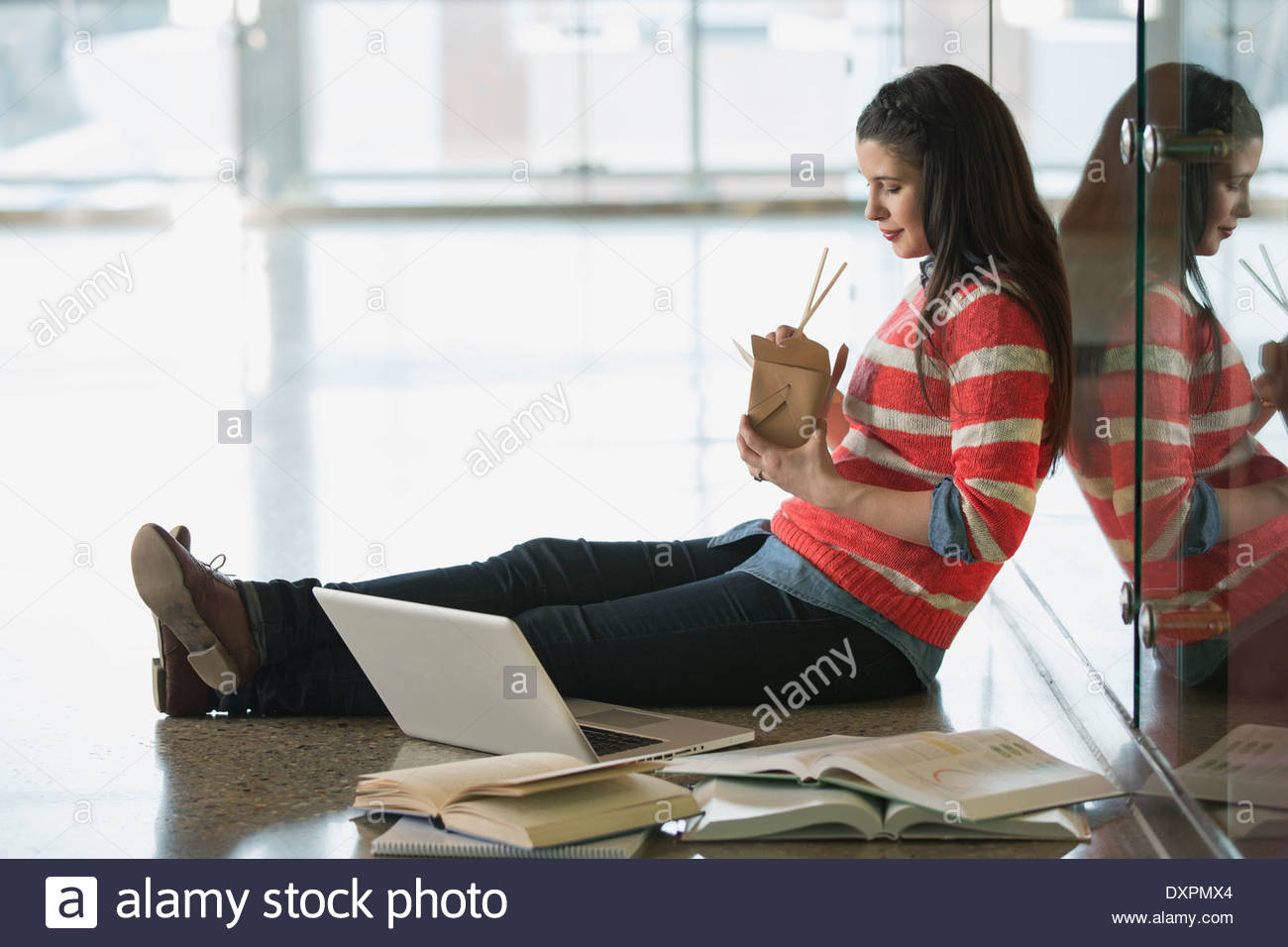 College student eating take-out food near laptop on floor - Stock Image