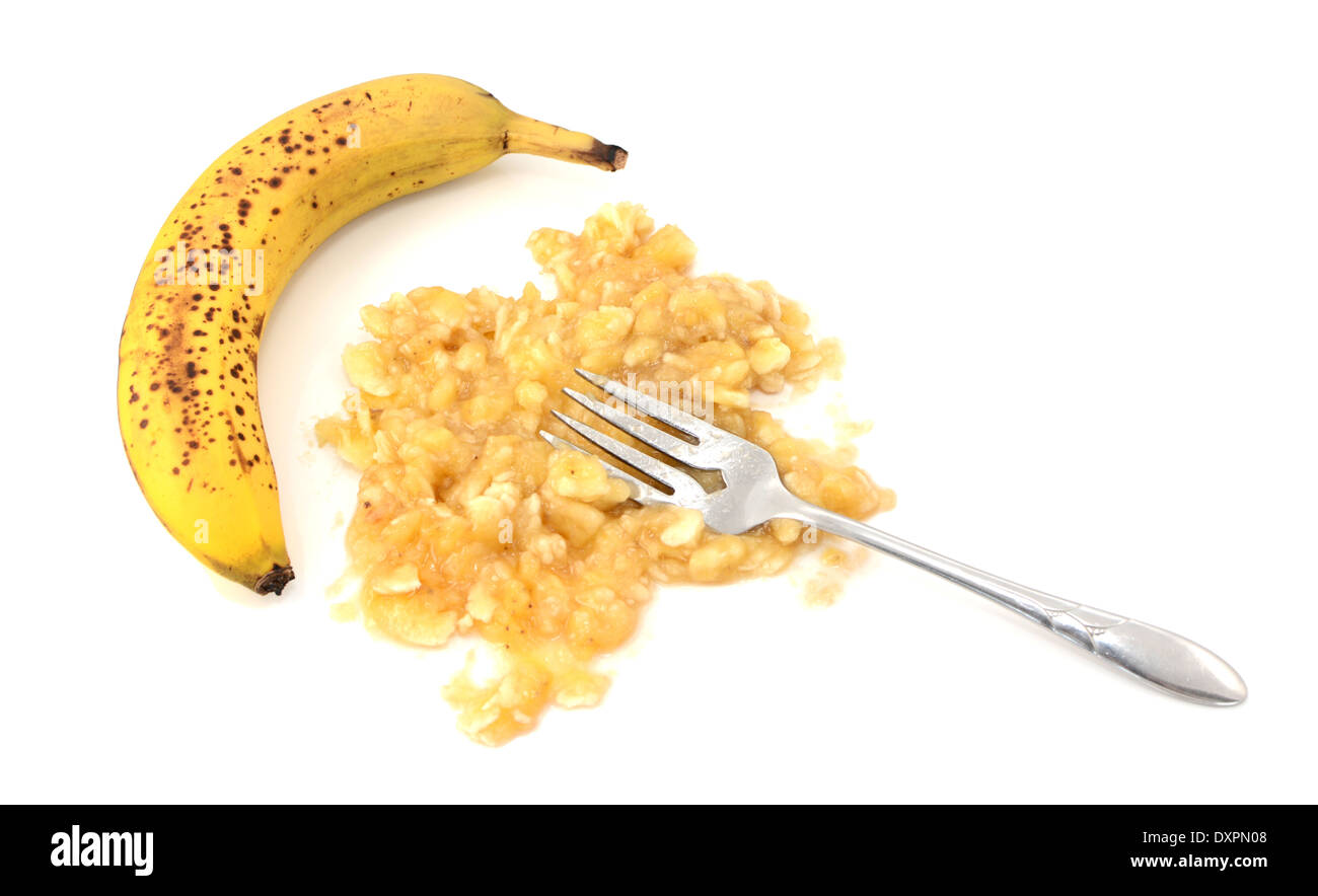 Overripe unpeeled banana with fork and pureed fruit, isolated on a white background - Stock Image