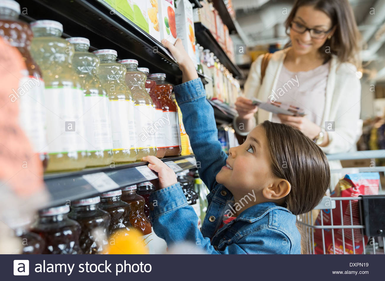Girl reaching for juice on shelf in market - Stock Image