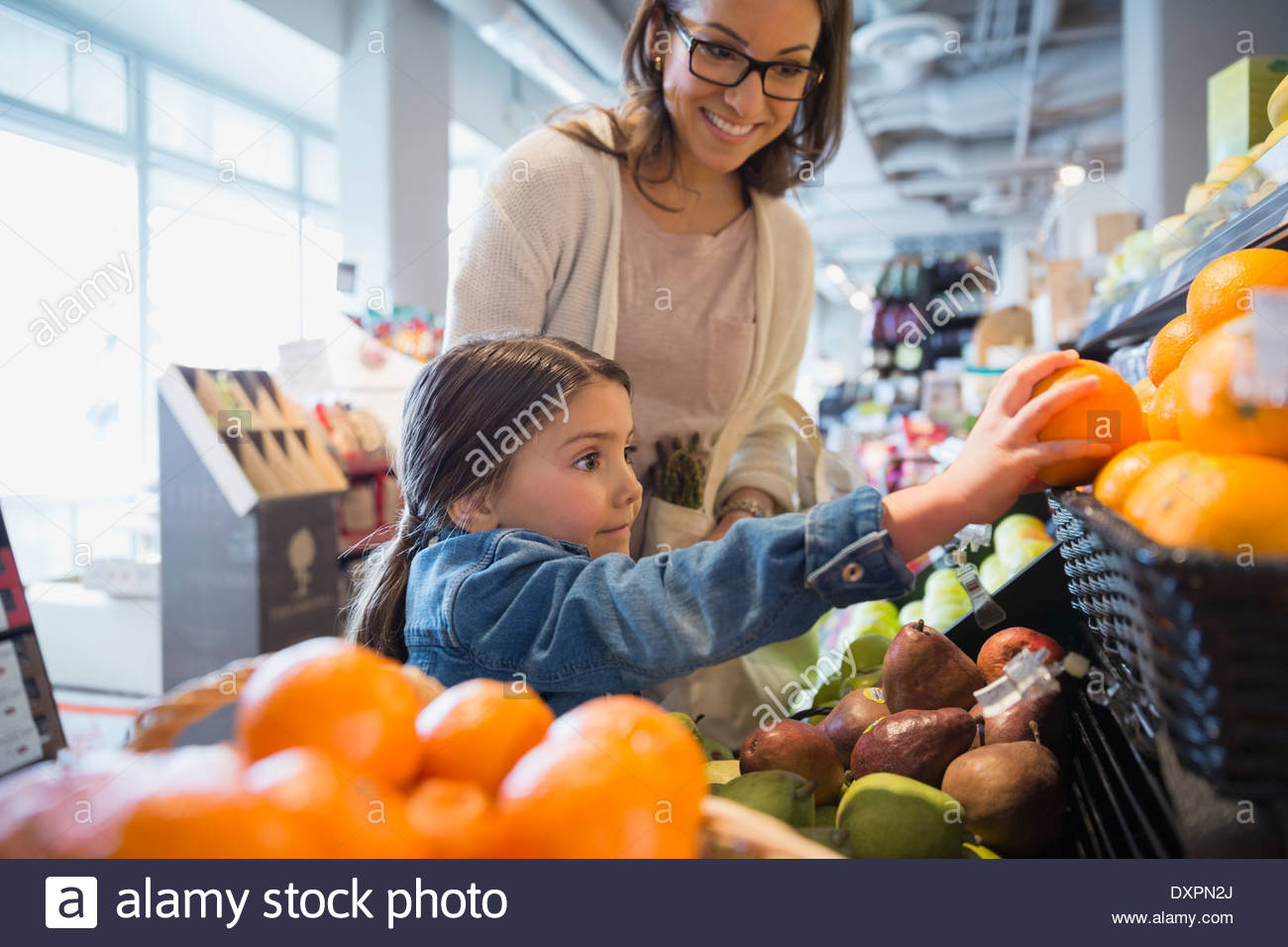 Mother watching daughter reach for orange in market - Stock Image
