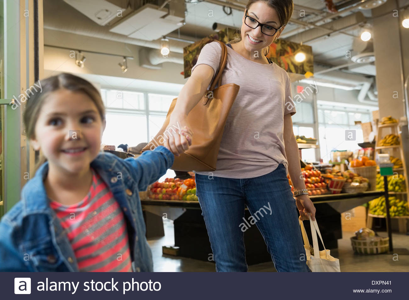 Daughter pulling mothers arm in market - Stock Image
