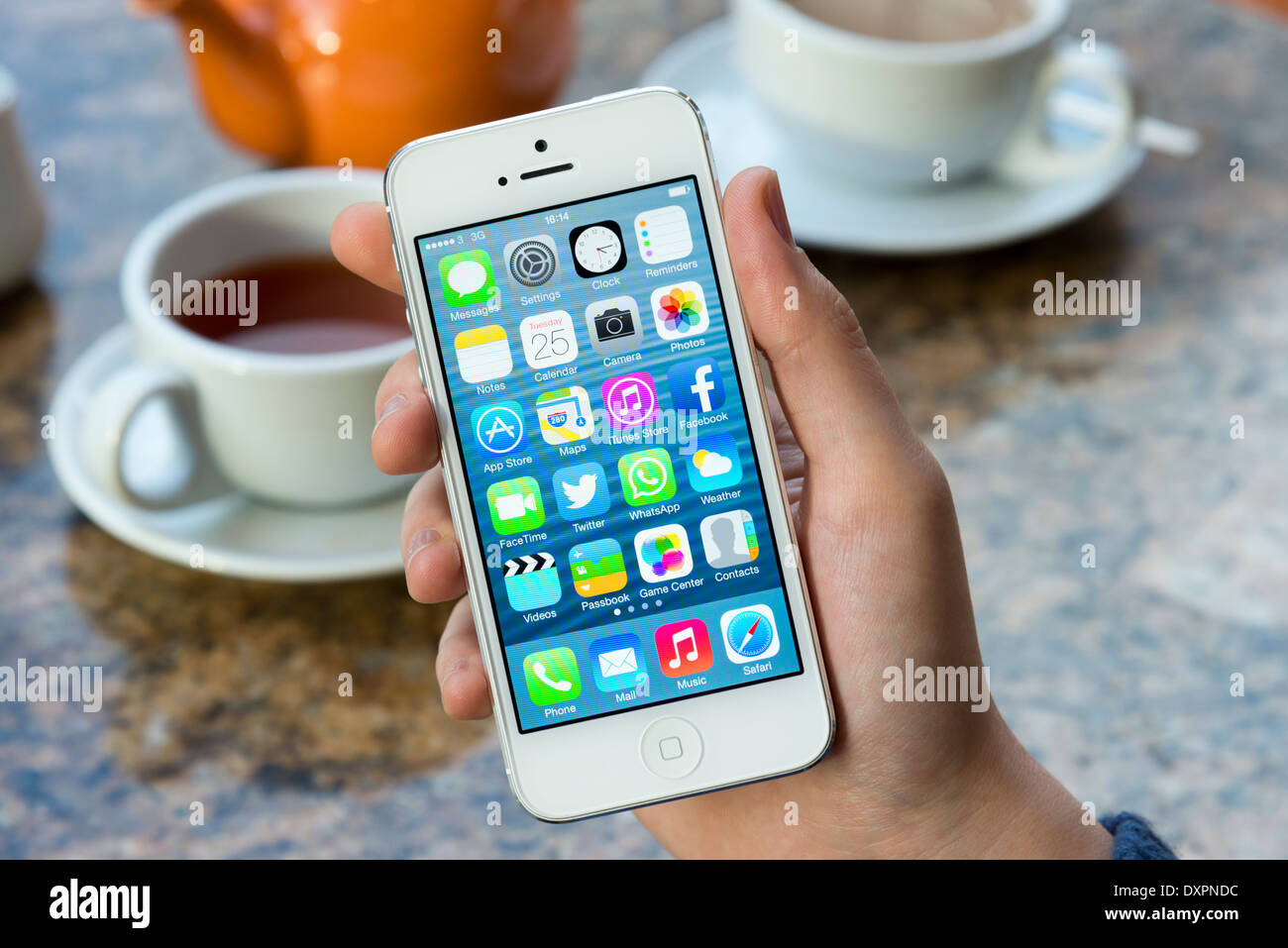 iOS 7 home screen of white Apple iPhone 5 in a cafe - Stock Image