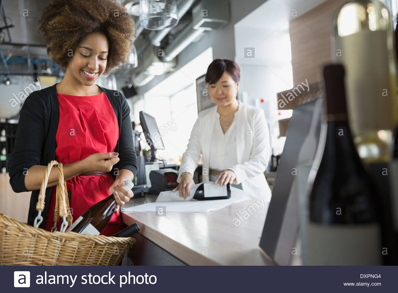 Woman purchasing wine in store - Stock Image