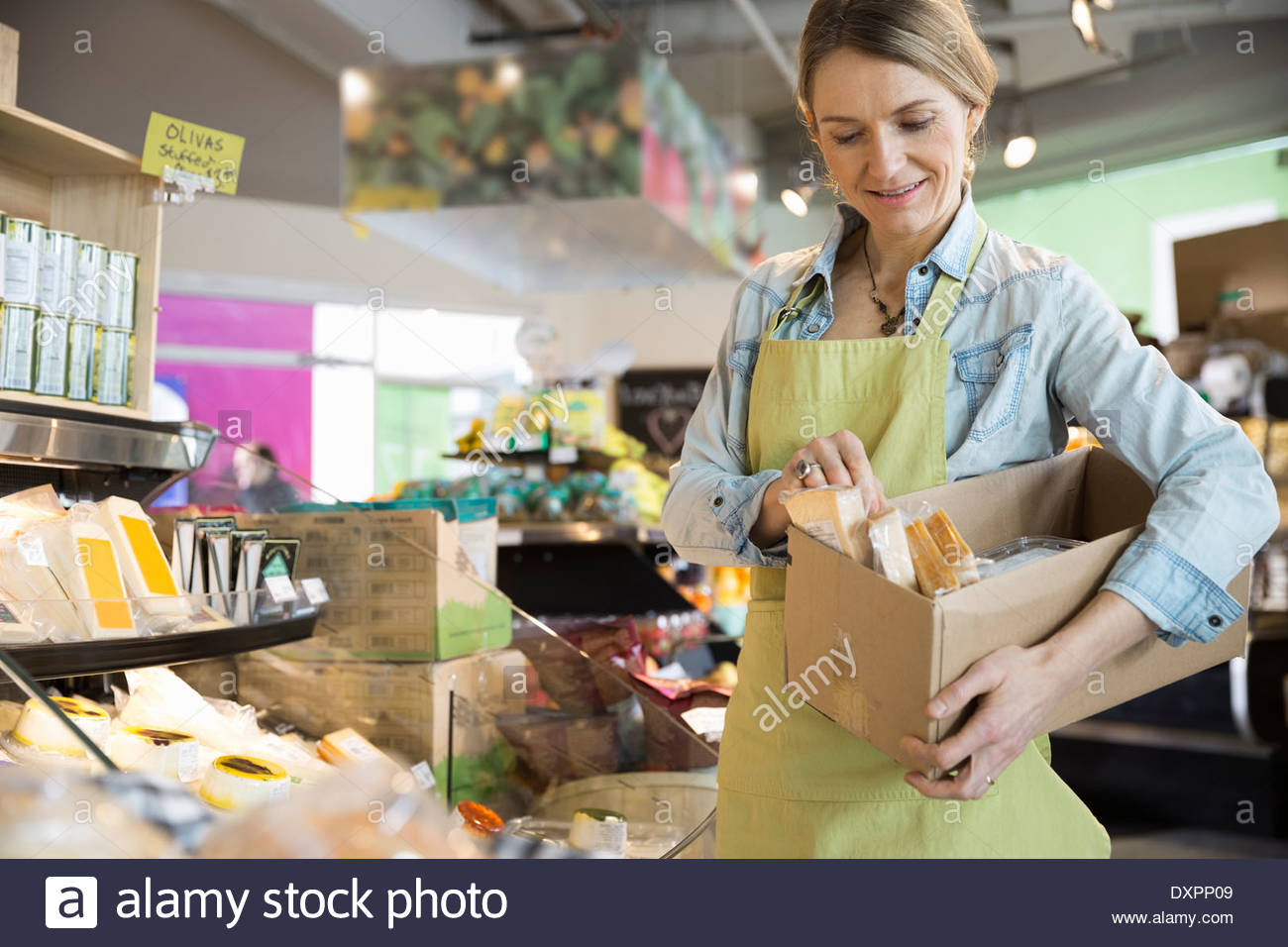 Worker stocking cheese in market - Stock Image