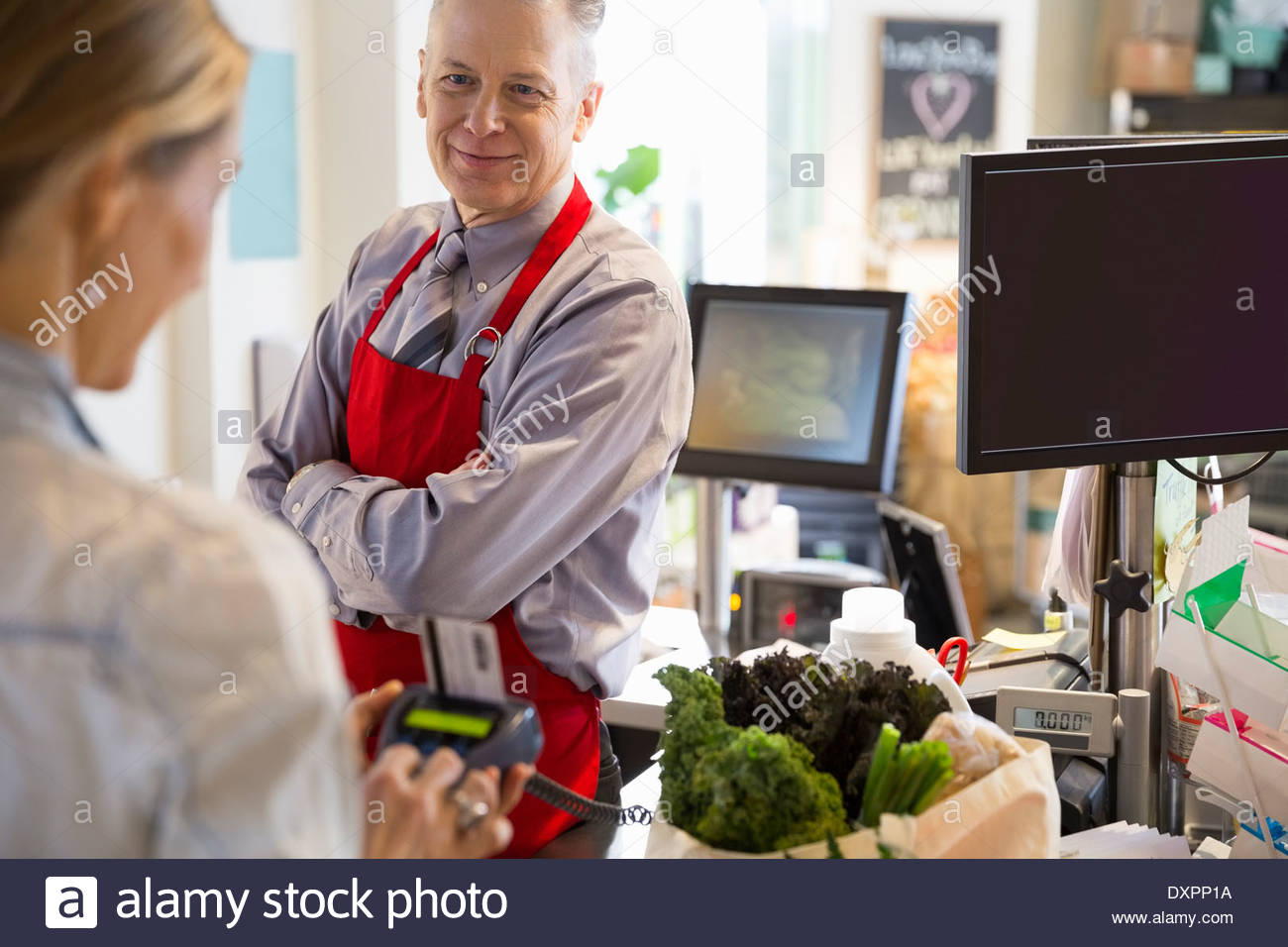 Woman paying clerk for groceries in market - Stock Image