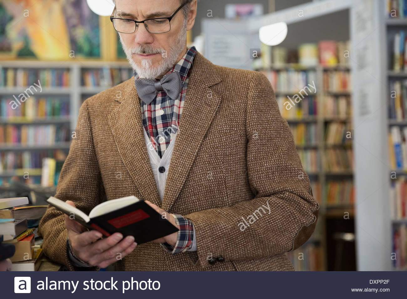 Man in bowtie reading book in bookstore - Stock Image