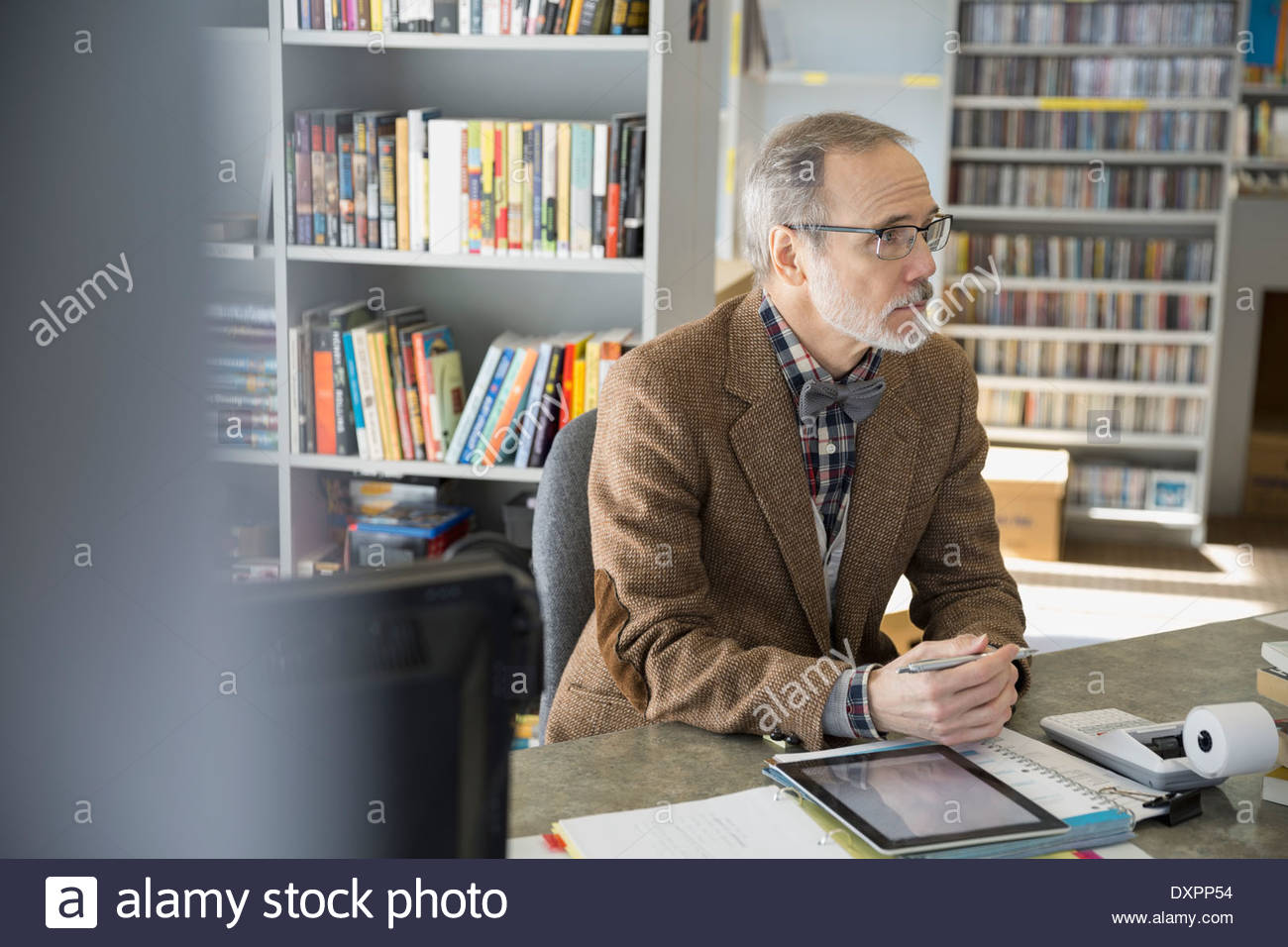 Bookstore owner sitting at counter - Stock Image