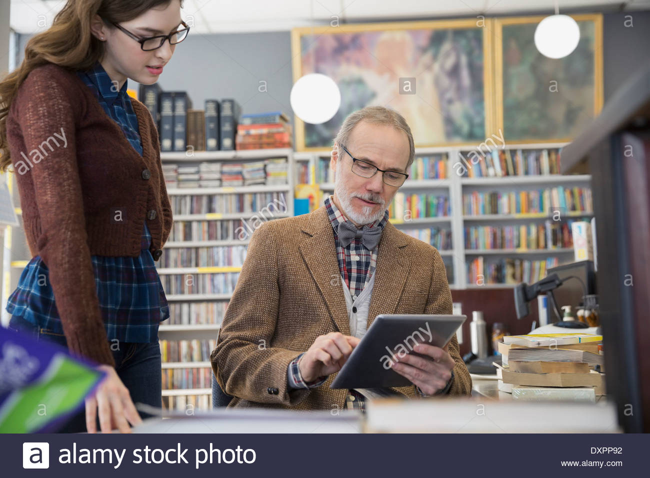 Woman watching bookstore owner using digital tablet - Stock Image