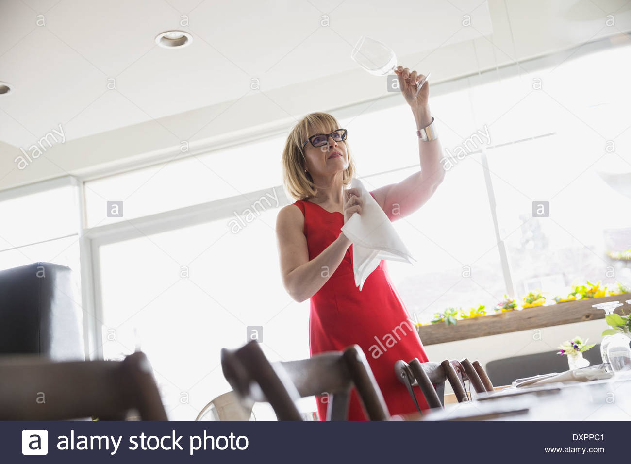 Bistro owner checking wine glasses Stock Photo