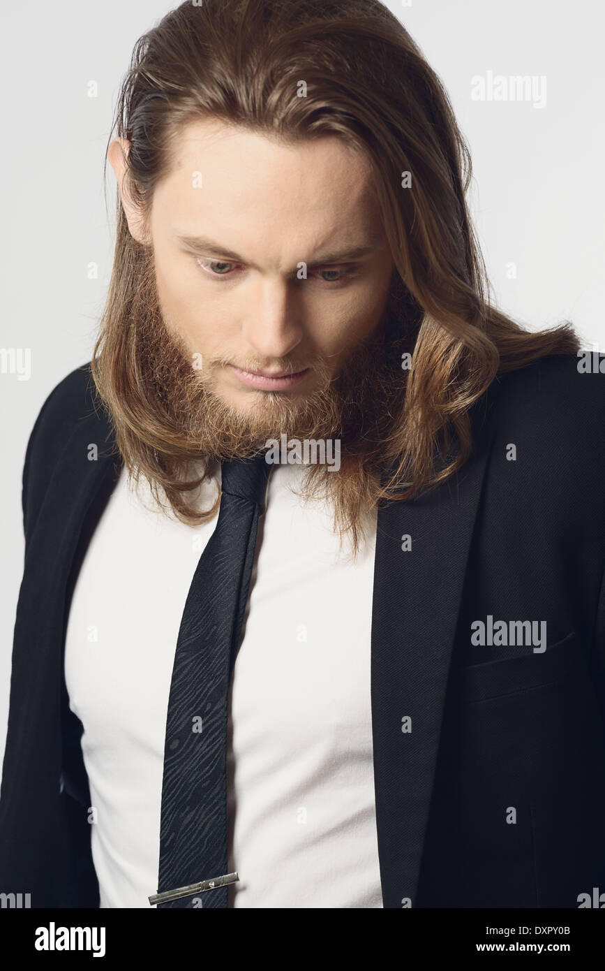 A long hair man male model with beard wearing necktie and suit close up portrait looking down
