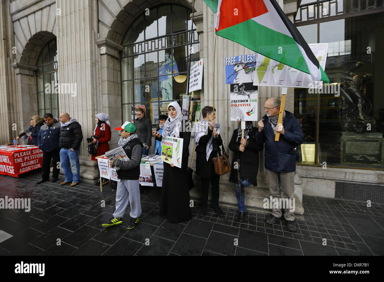 Dublin, Ireland. 29th March 2014. Activists from the Ireland Palestine Solidarity Campaign stand outside the GPO (General Post Office), holding Palestinian flags and posters. The Ireland Palestine Solidarity Campaign (IPSC) protested in Dublin's O'Connell Street on the 38th anniversary of the 1976 land day protest against discrimination of Palestinians by Israel and the expansion of Israeli settlements in Palestinian territory. Credit:  Michael Debets/Alamy Live News - Stock Image