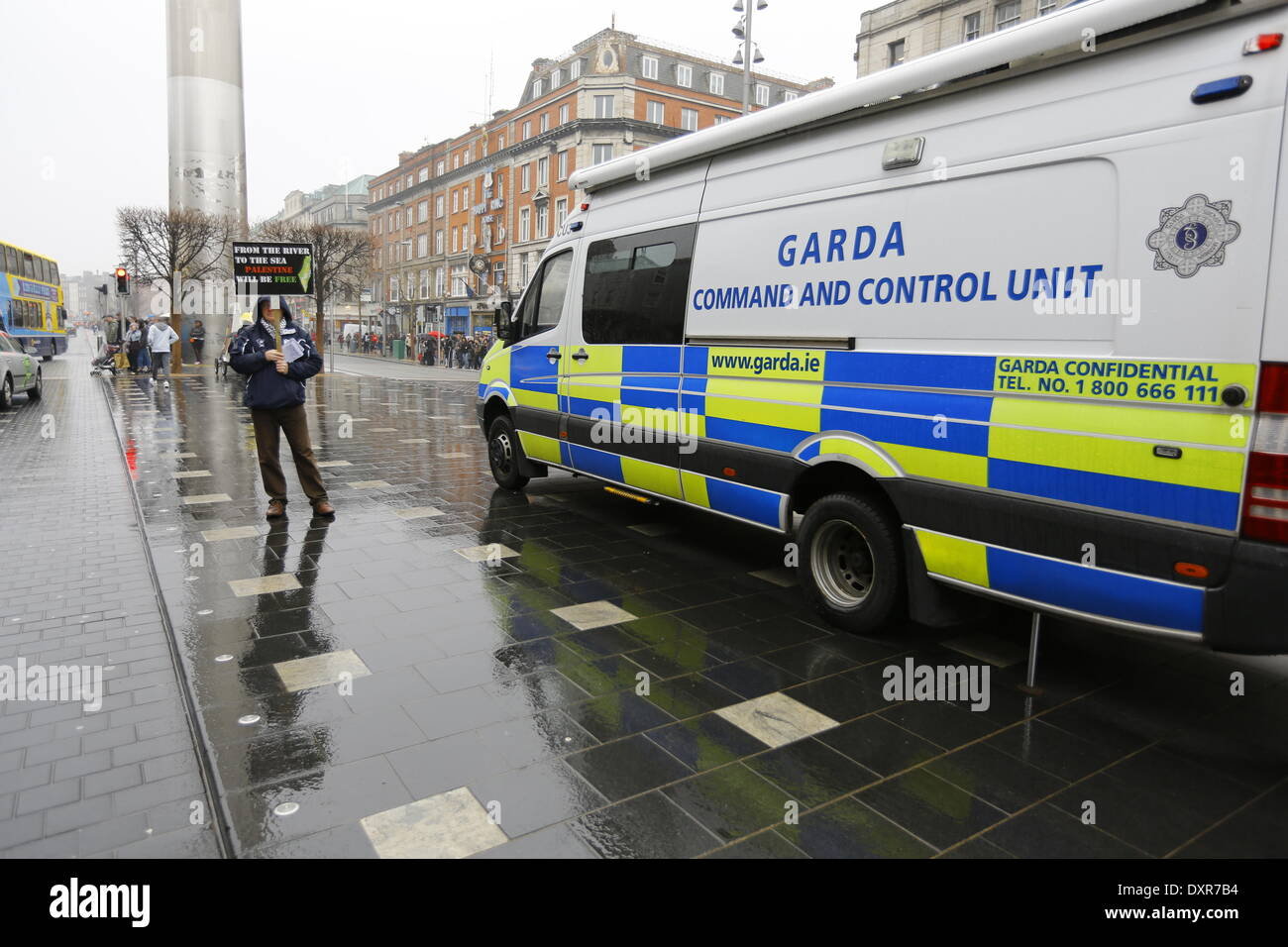 Dublin, Ireland. 29th March 2014. An activists stands next to a Garda (Irish Police) Command and Control Unit van, holding a poster that reads 'From the river to the sea, Palestine will be free'. The Ireland Palestine Solidarity Campaign (IPSC) protested in Dublin's O'Connell Street on the 38th anniversary of the 1976 land day protest against discrimination of Palestinians by Israel and the expansion of Israeli settlements in Palestinian territory. Credit:  Michael Debets/Alamy Live News - Stock Image