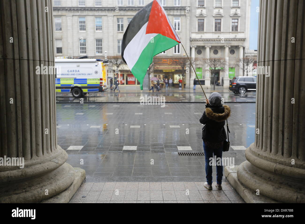 Dublin, Ireland. 29th March 2014. A protester waves an Palestinian flag. The Ireland Palestine Solidarity Campaign (IPSC) protested in Dublin's O'Connell Street on the 38th anniversary of the 1976 land day protest against discrimination of Palestinians by Israel and the expansion of Israeli settlements in Palestinian territory. Credit:  Michael Debets/Alamy Live News - Stock Image