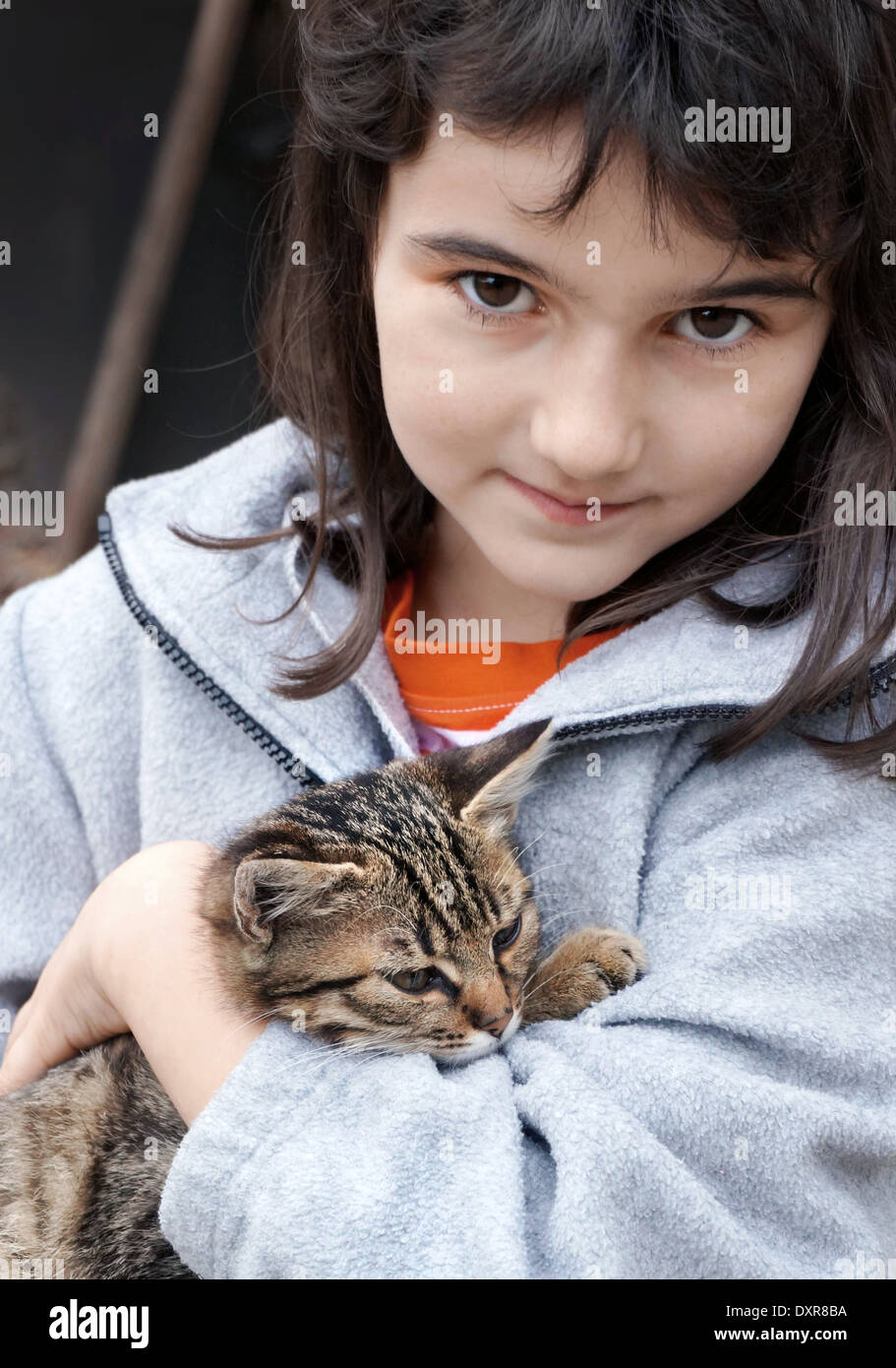 A cute little eight years old girl takes care of a cute kitten Stock Photo