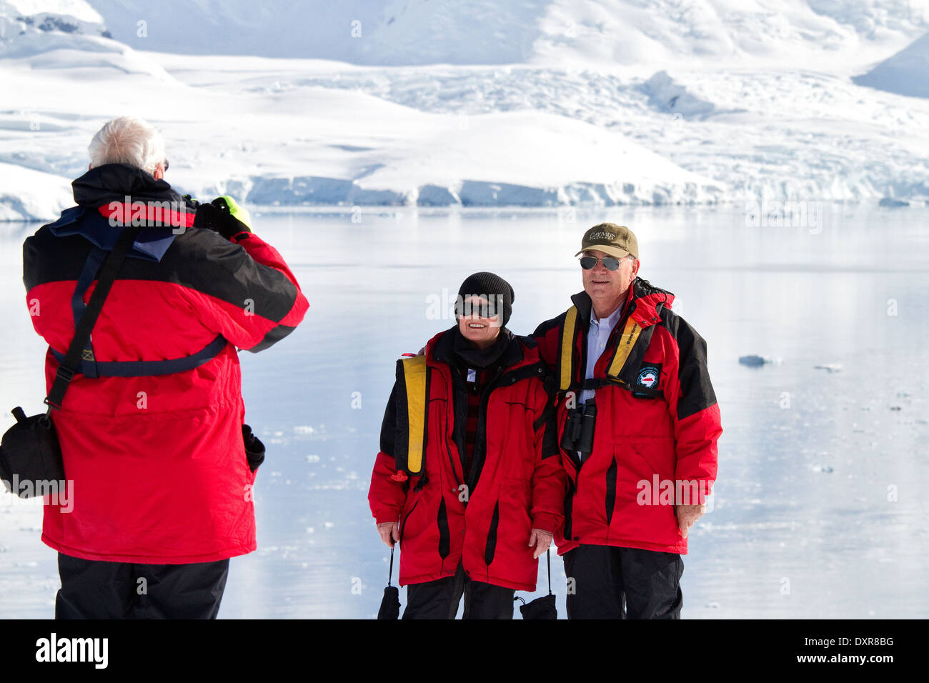 Antarctica tourists on cruise pose for camera in front of beautiful Antarctic landscape of glacier and iceberg. - Stock Image