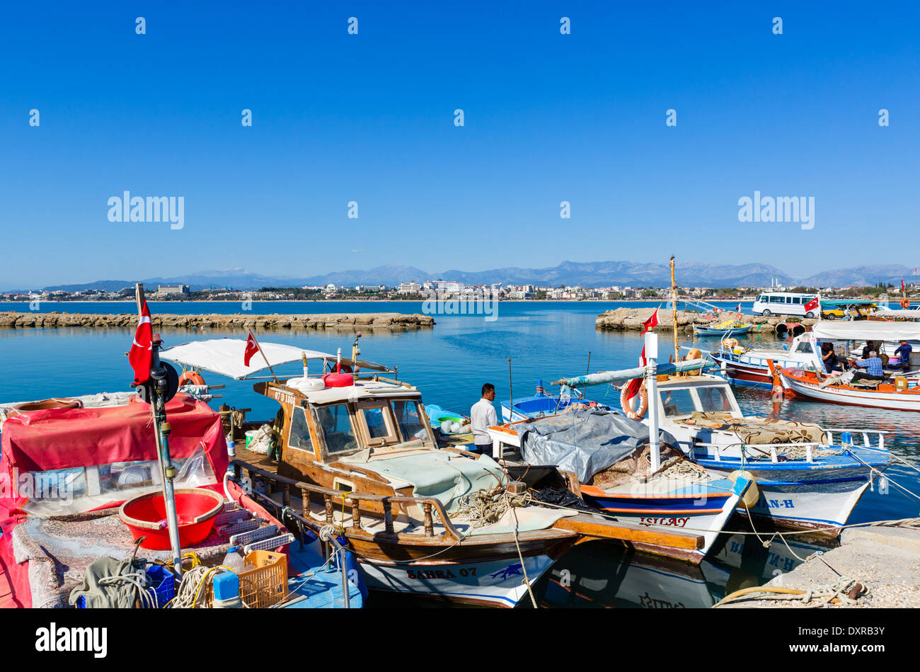 Fishing boats in the old town harbour looking towards beaches and hotel zone to west of the town, Side, Antalya Province, Turkey - Stock Image