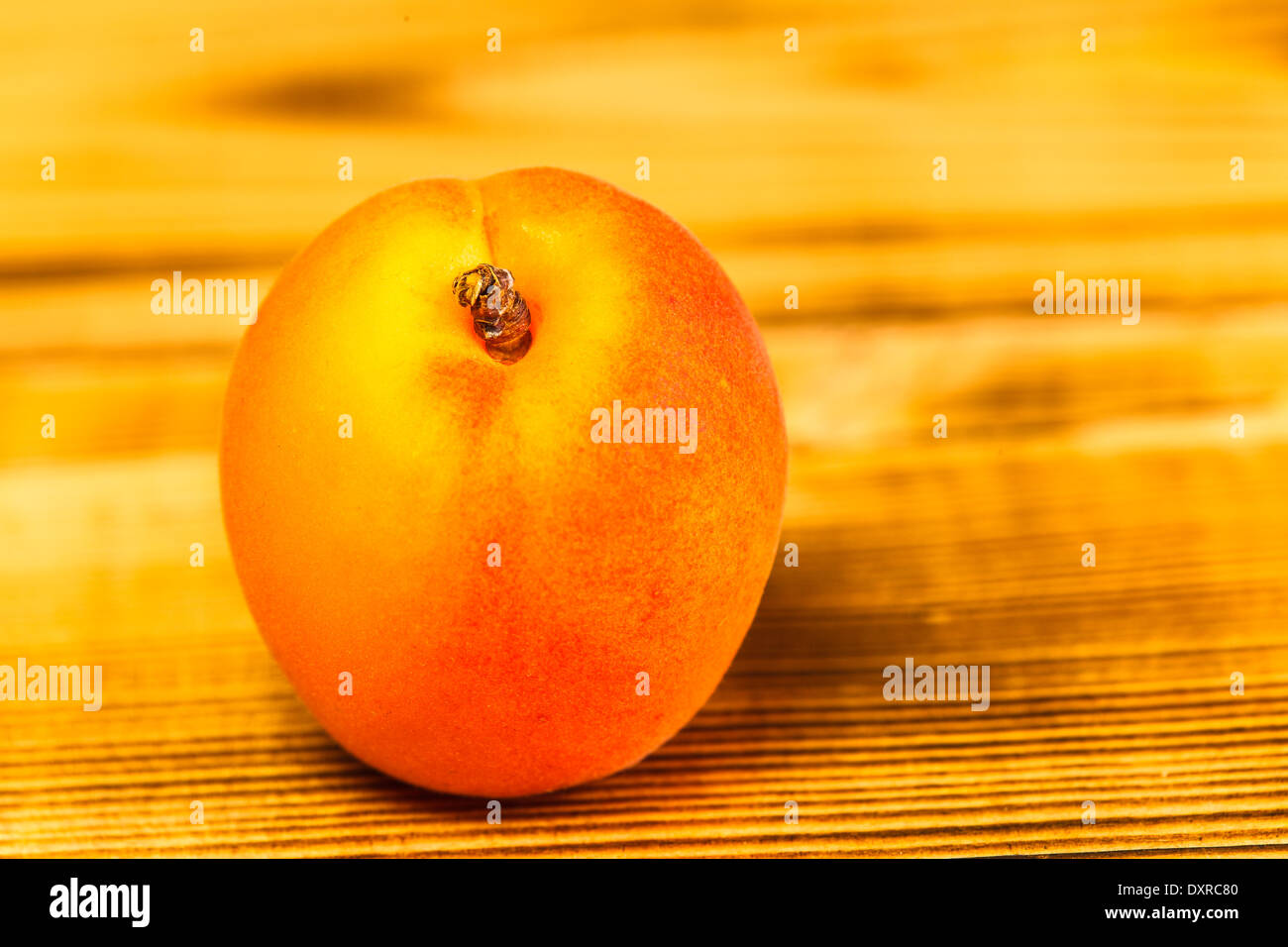 Apricot on wooden table, close-up - Stock Image