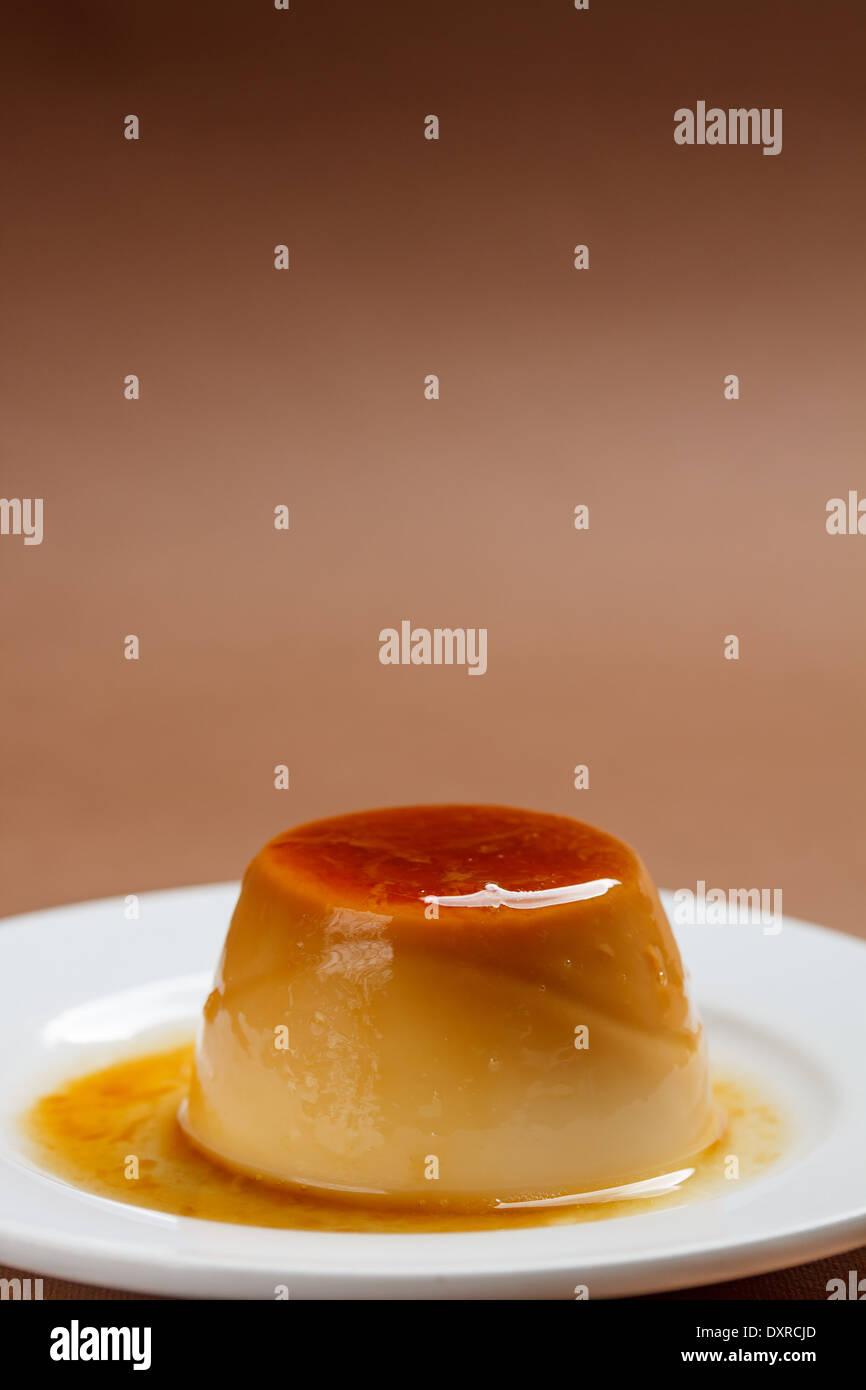 Caramel custard flan in a white plate - Stock Image