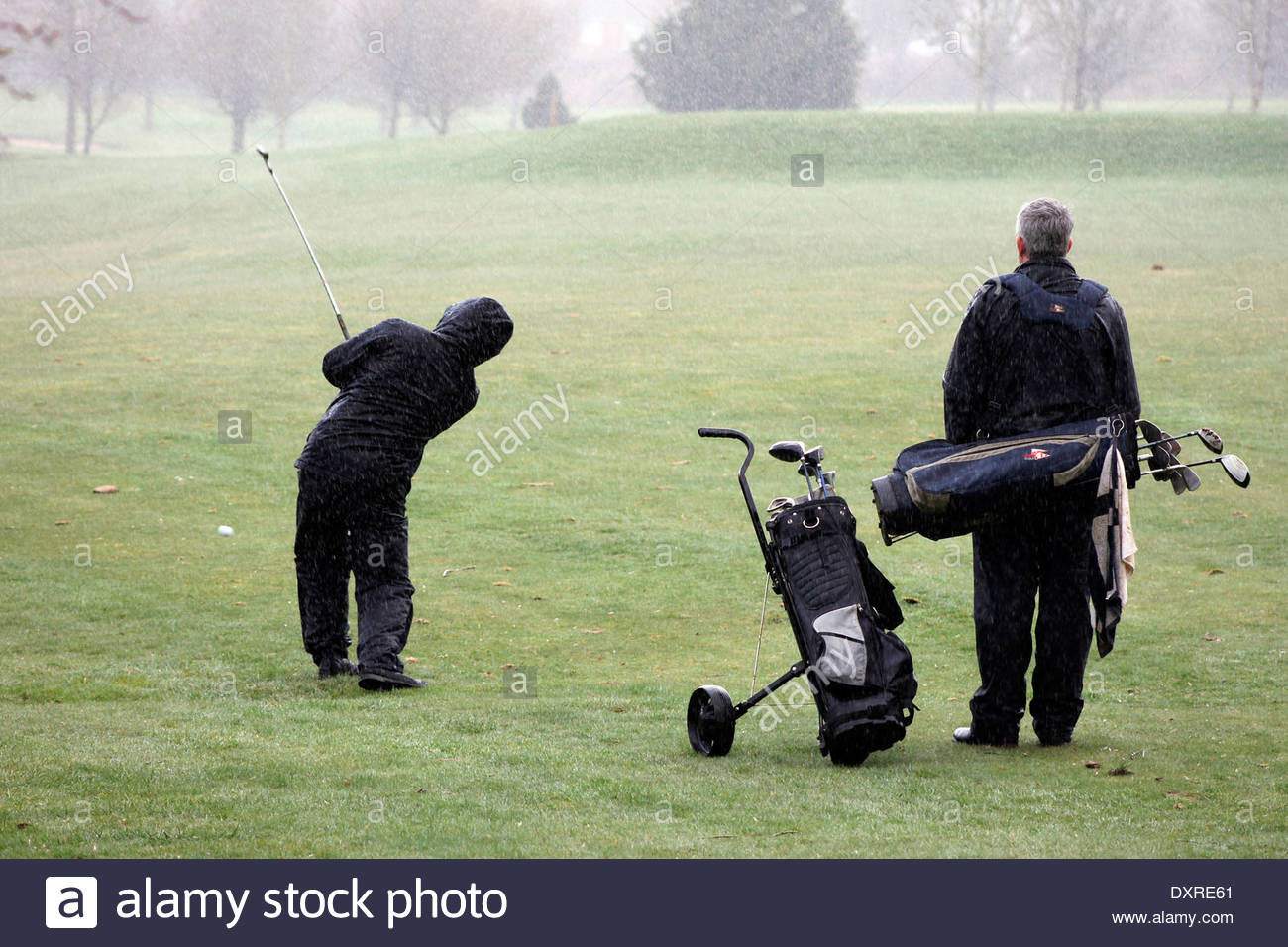 Playing a round of golf in the rain, in Gloucestershire, UK. - Stock Image