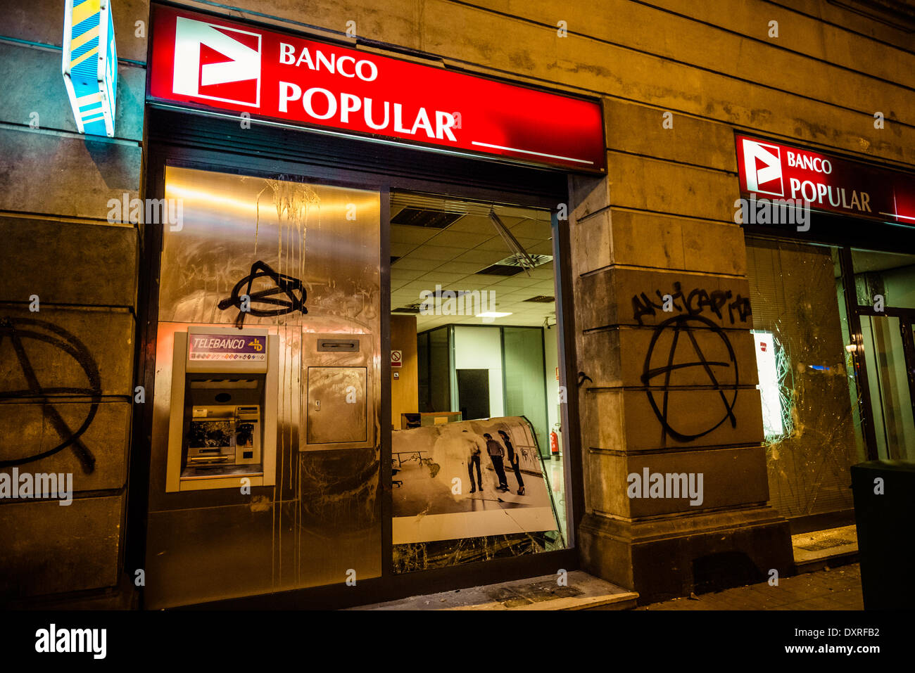 Barcelona, Spain. March 29th, 2014: A 'Banco Popular' bank office gets destroyed during a march through Barcelona to sympathize with twenty activists facing a national court law suit Credit:  matthi/Alamy Live News - Stock Image