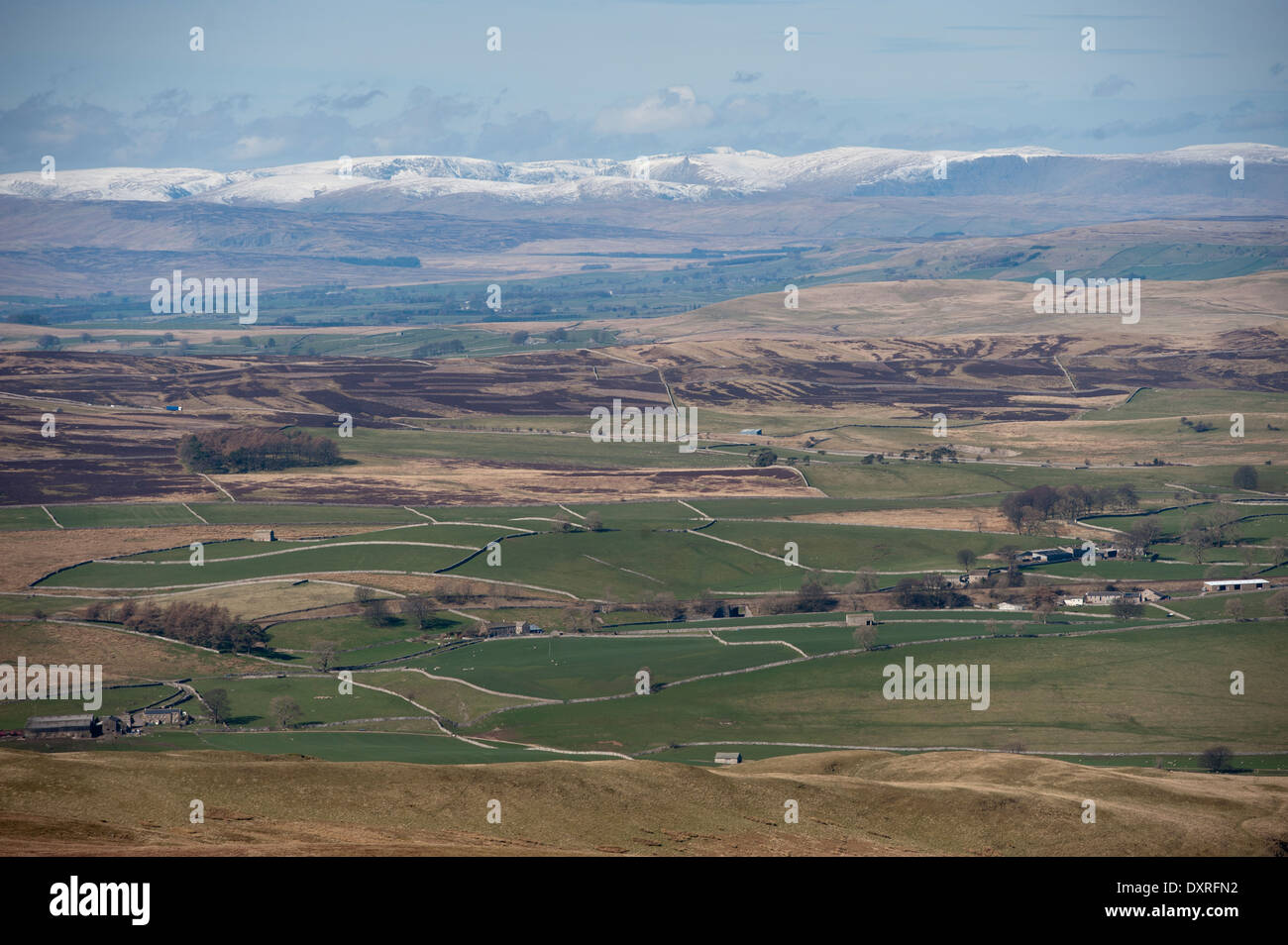 Looking over the Upper Eden Valley towards snow covered hills of the Lake District. Cumbria, UK - Stock Image