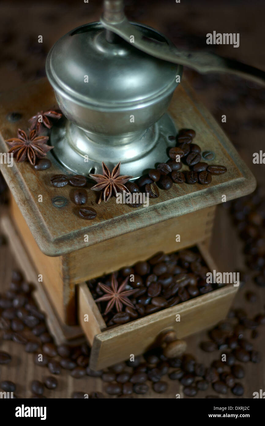 Old coffee mill with coffee beans and star anise. Selective focus. - Stock Image