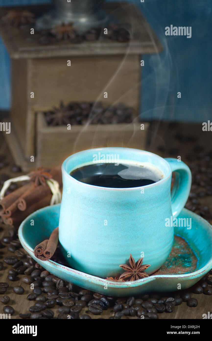 Coffee in the teal mug and old coffee mill with cinnamon and star anise. Selective focus. - Stock Image