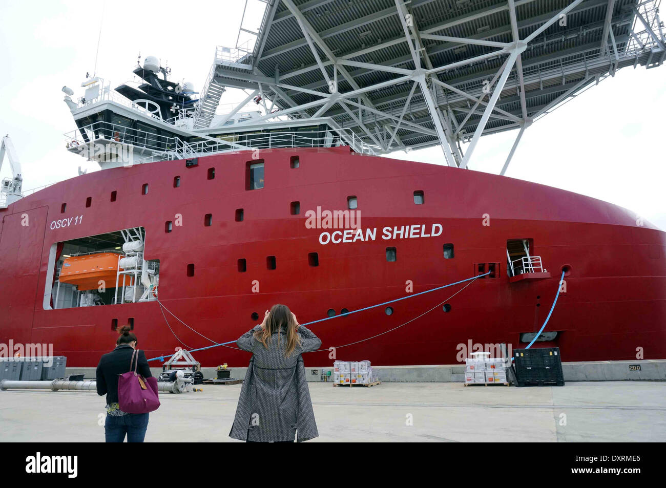Perth, Australia . 30th Mar, 2014. A woman takes photo of Australian Defence Vessel Ocean Shield which is loaded with supplies and equipments before heading for a tasked area to locate the black box pinger of the missing Malaysia Airlines Flight MH370, at HMAS Stirling naval base near Perth, Australia, March 30, 2014. Credit:  Xinhua/Alamy Live News - Stock Image