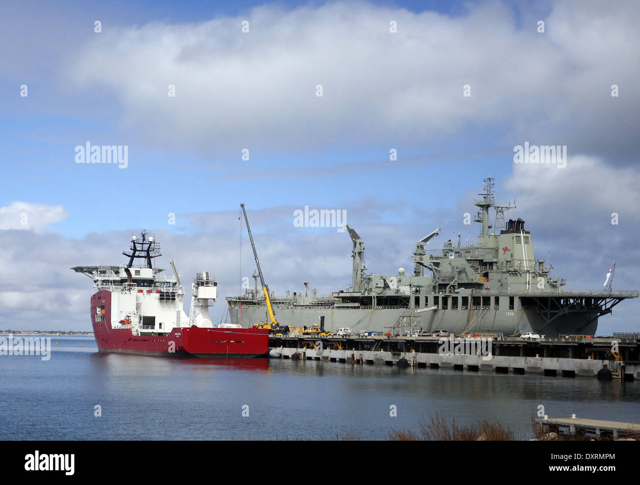 Perth, Australia . 30th Mar, 2014. Australian Defence Vessel Ocean Shield is loaded with supplies and equipments before heading for a tasked area to locate the black box pinger of the missing Malaysia Airlines Flight MH370, at HMAS Stirling naval base near Perth, Australia, March 30, 2014. Credit:  Xinhua/Alamy Live News - Stock Image