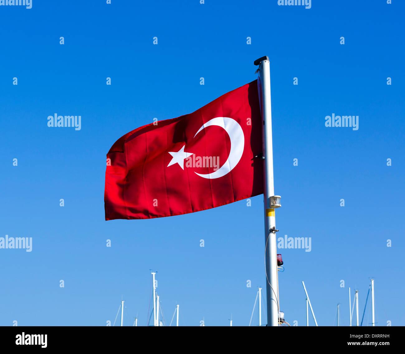 Turkish flag flying on a boat in the harbour at Ucagiz near Kekova Island, Turquoise Coast, Antalya Province, Turkey - Stock Image