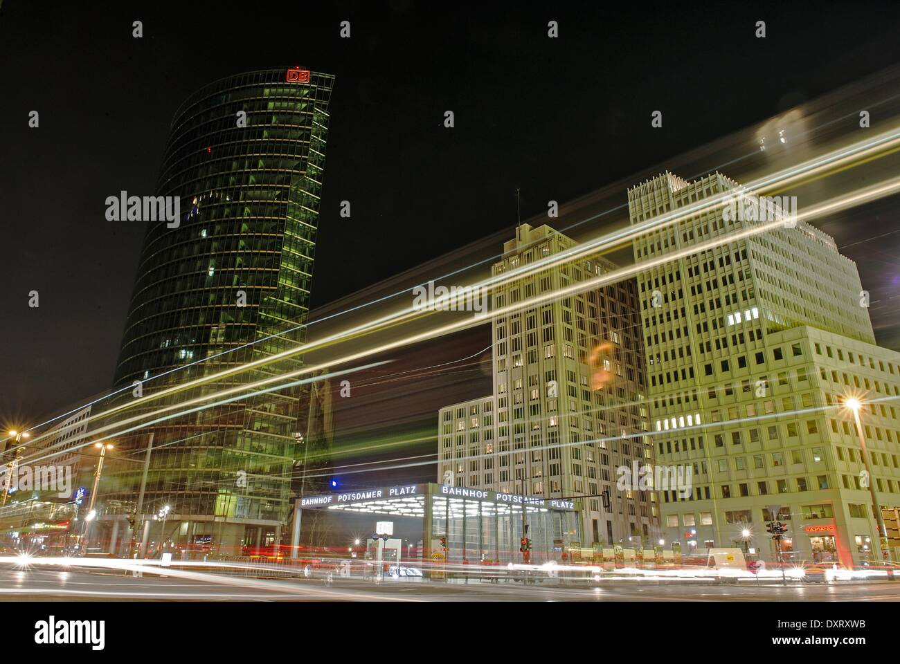 Berlin, Germany. 29th Mar, 2014. Bus services and cars pass by the unlit office highrise offices of the Deutsche Bahn (DB) during the so called 'Earth Hour' event at Potsdamer Platz in Berlin, Germany, 29 March 2014. 'Earth Hour' is a worldwide event which aims to set a sign for environmental protection and to draw attention to environmental awareness. Photo: Henning Kaiser/dpa/Alamy Live News - Stock Image