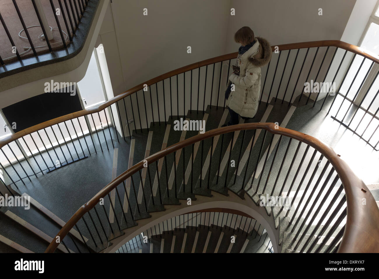 A Woman Walking Down A 1950u0027s Spiral Staircase In A Department Store