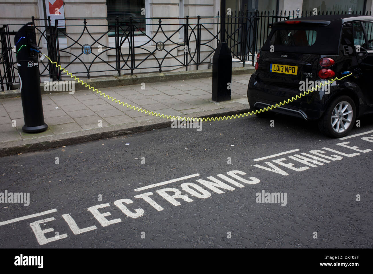 A parked Smart car recharges electric power at an EDF charging point in central London. Stock Photo