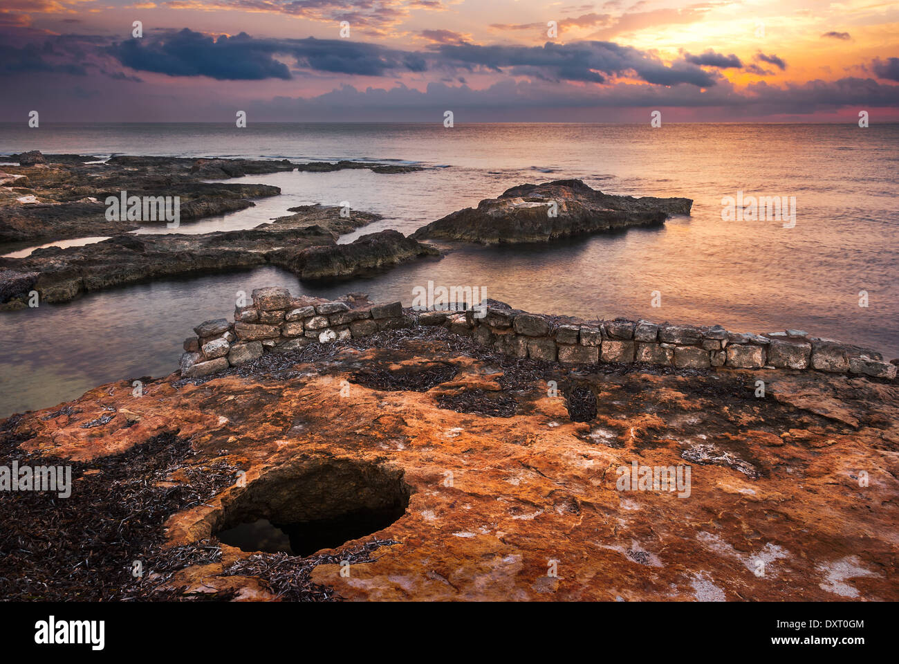 Sunset over the Sea and Rocky Coast with Ancient Ruins in Mahdia, Tunisia Stock Photo