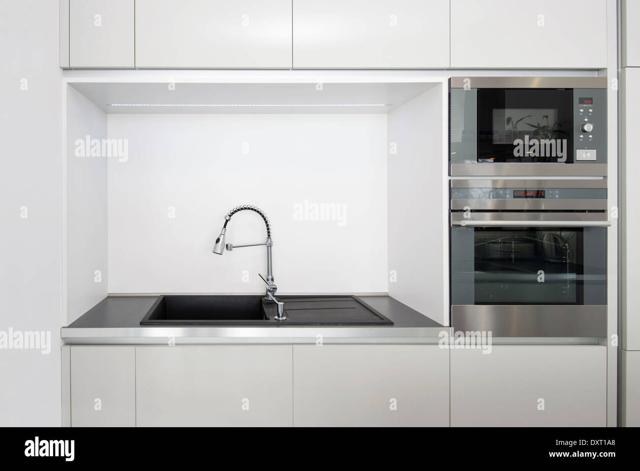 Detail Of Kitchen Built In Appliances And Faucet With Sink