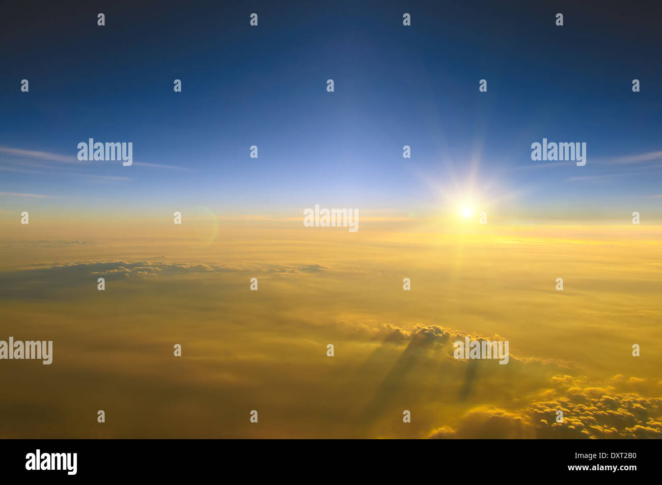 Spectacular view of a sunset above the clouds from airplane window - Stock Image