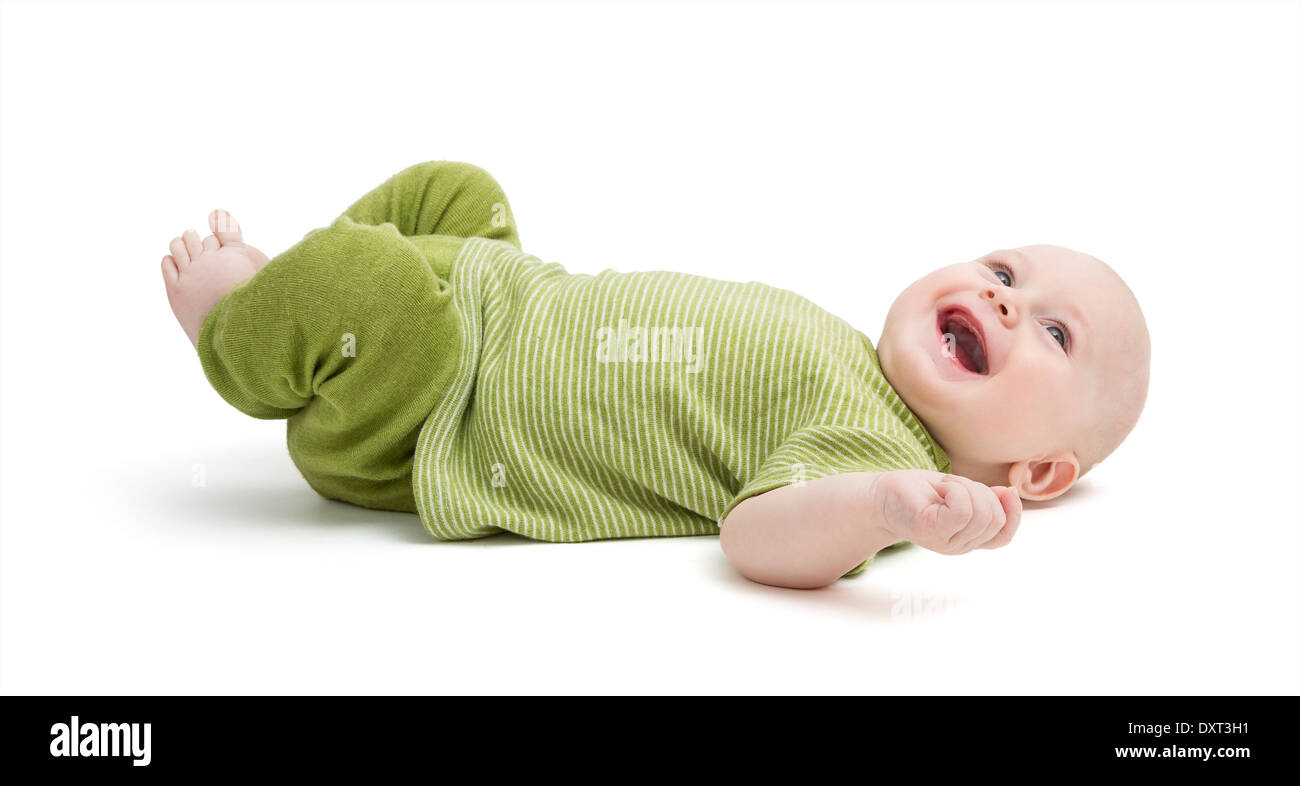 happy, laughing toddler laying on back isolated on white background - Stock Image