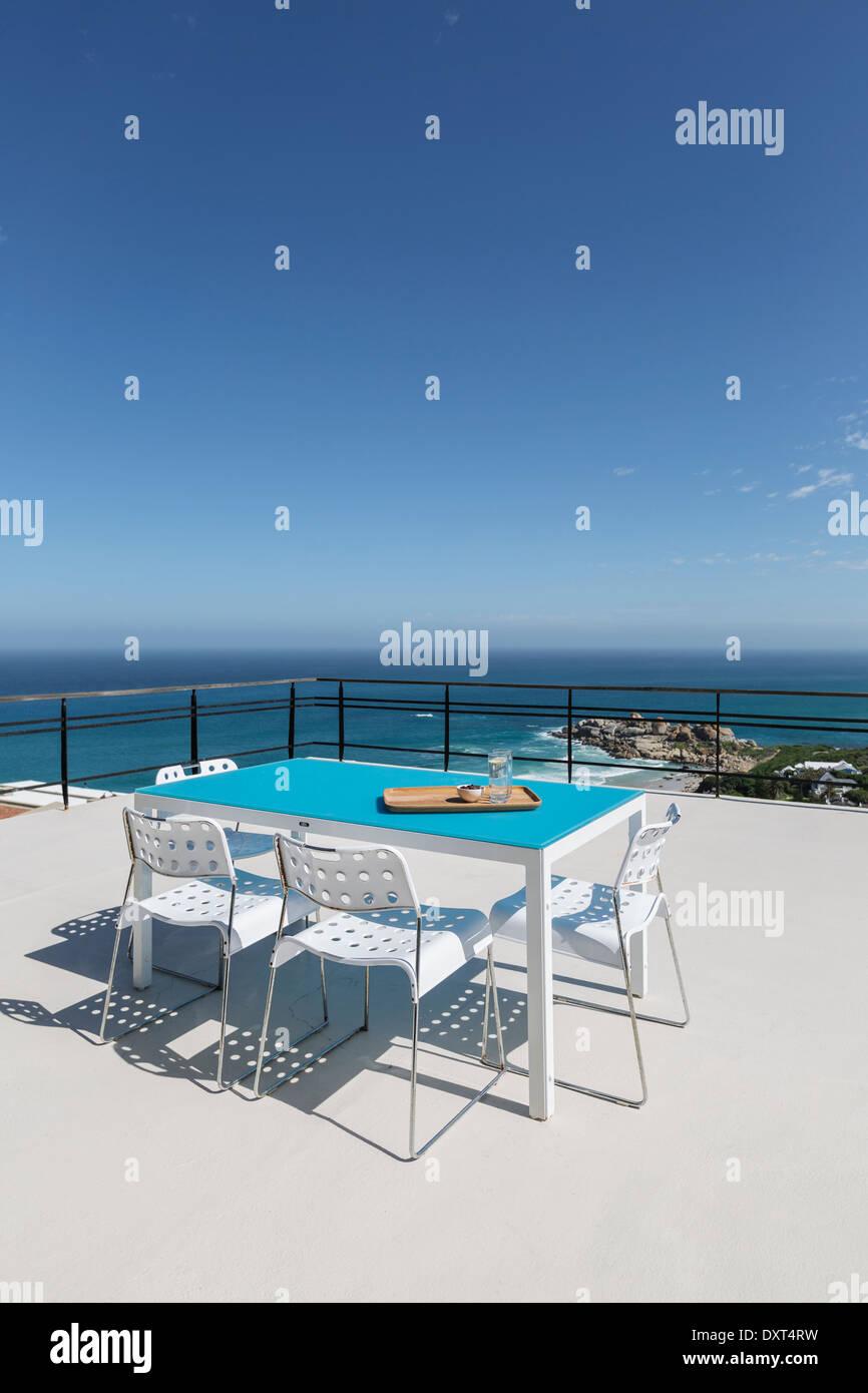 Table on patio overlooking ocean - Stock Image