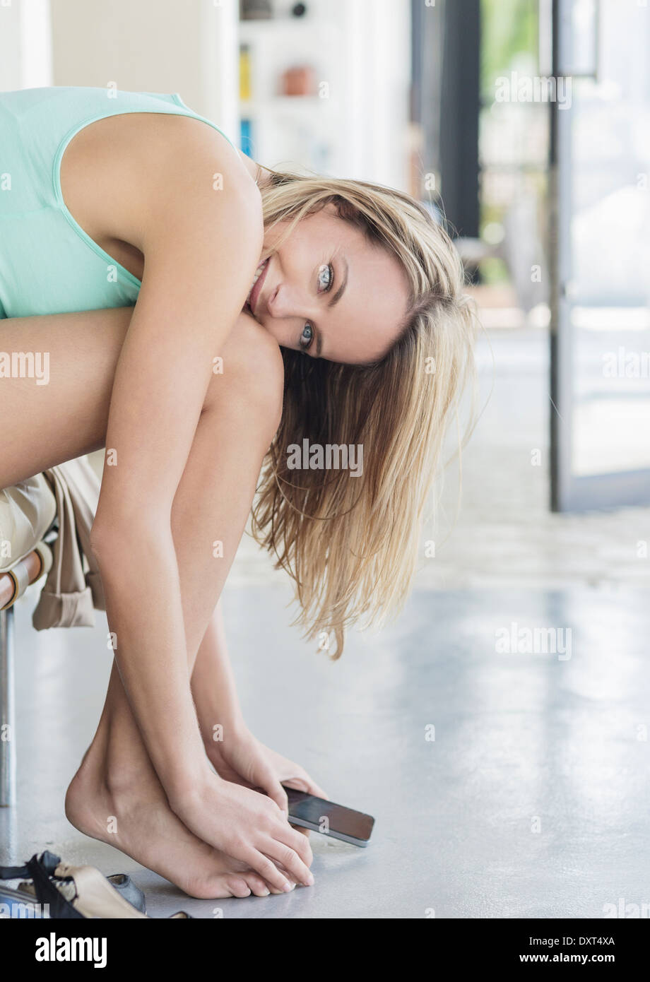 Portrait of woman leaning over legs - Stock Image
