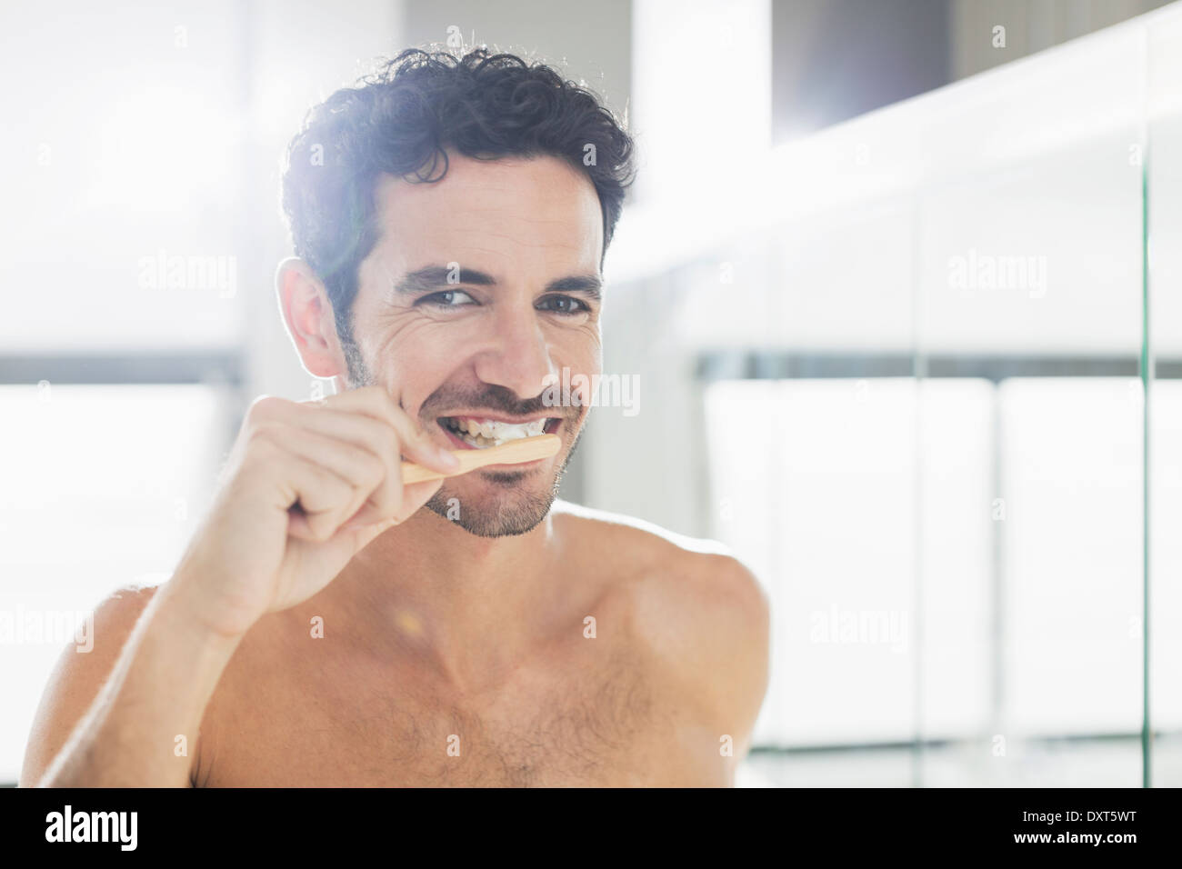 Portrait of man brushing teeth - Stock Image
