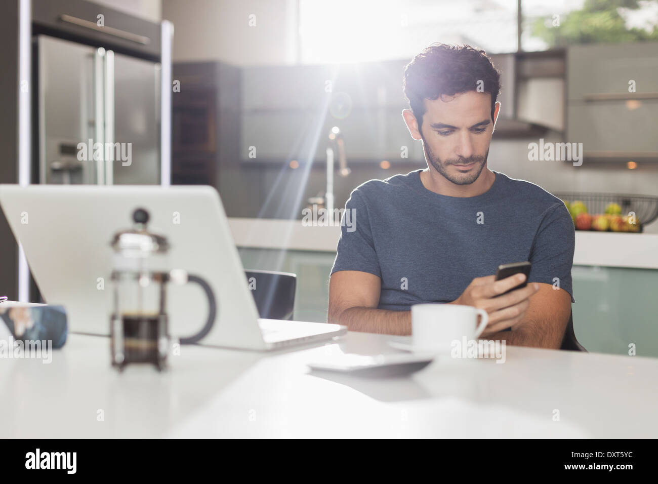 Man texting with cell phone at kitchen table - Stock Image
