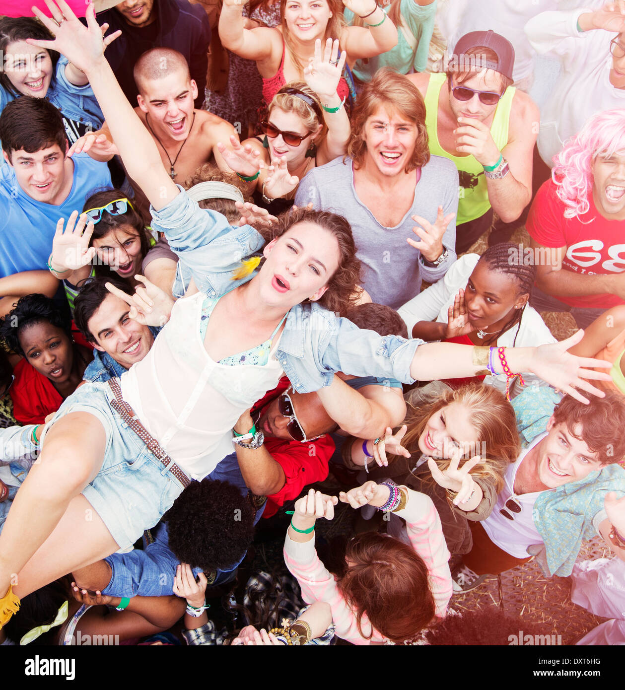Enthusiastic woman crowd surfing at music festival Stock Photo