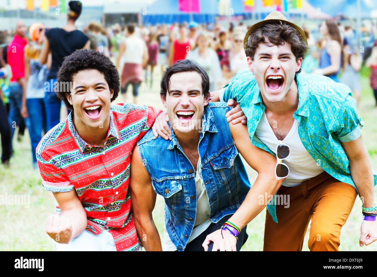 Enthusiastic men cheering at music festival - Stock Image