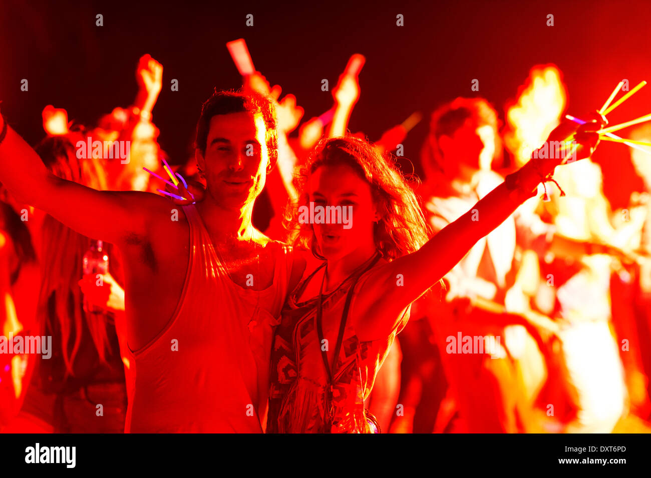 Portrait of couple with glow sticks dancing at music festival - Stock Image