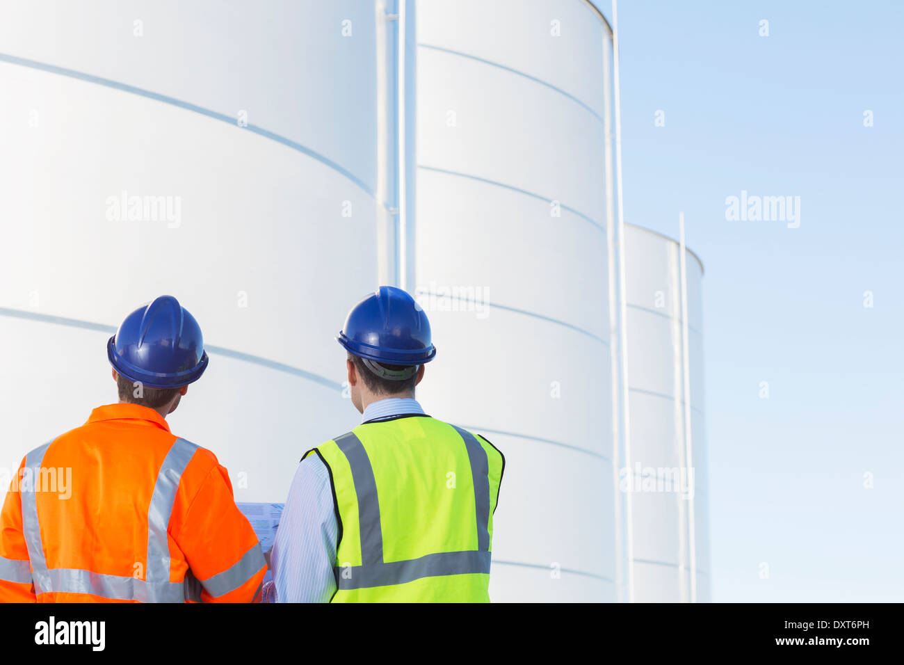 Workers looking up at silage storage towers - Stock Image